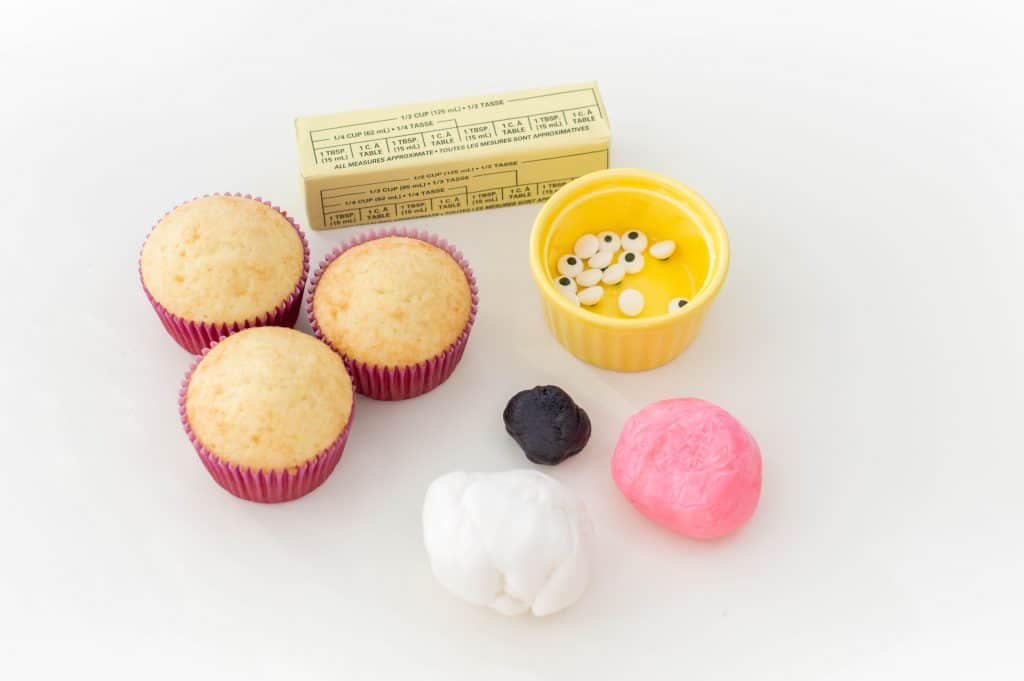 12 of your favorite vanilla cupcakes ½ cup softened butter 2 cups icing sugar 3-4 tbsp milk 8-9 oz. white fondant 12 candy googly eyes 4-6 oz. pink fondant 1-2 oz. black fondant  Yields: One dozen cupcakes  Begin by checking on your cupcakes: they have to be completely cool before you begin the decorating process.  Using an electric mixer, make your butter cream by beating together butter, sugar and milk on medium speed.  Gradually increase speed to high.  Once the buttercream is formed, scoop it into a piping bag and frost the center of each cupcake (use a round icing tip).  Separate your white fondant into 24 spheres, about one inch in size each.  Flatten out the white fondant spheres and then point one end. They will act as your bunnies' ears.  Roll out a portion of your pink fondant into 24 small spheres, about 1/3 of an inch in size.  Flatten the pink spheres, slightly smaller than your white fondant pieces. Point one end and press one onto each white fondant piece.  Insert a toothpick into each fondant bunny ear.  With the remainder of your pink fondant, roll out 12 small spheres, about ¼ of an inch thick. Place one on the middle of the frosting of each cupcake. Above it, place 2 of your googly candy eyes.  Roll out small, thin strips of your black fondant – you'll need 48 of them.  Place the black strips on your bunnies' faces – 2 on either side of its nose.  Gently insert 2 fondant bunny ears on the top of each cupcake. Serve, enjoy and Happy Easter!